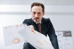 Βέβαιος επιχειρηματίας που ρίχνει το έγγραφο περίπου στο γραφείο Στοκ εικόνα με δικαίωμα ελεύθερης χρήσης