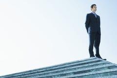 Βέβαιος επιχειρηματίας που στέκεται στη μαρμάρινη σκάλα Στοκ Εικόνες
