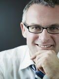 Βέβαιος επιχειρηματίας που χαμογελά στη φωτογραφική μηχανή Στοκ Εικόνες