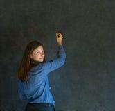 Γυναίκα που γράφει στο σκοτεινό υπόβαθρο πινάκων Στοκ εικόνα με δικαίωμα ελεύθερης χρήσης