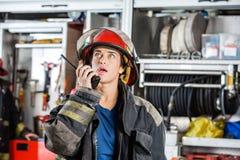 Βέβαιος θηλυκός πυροσβέστης που χρησιμοποιεί την ομιλούσα ταινία Walkie Στοκ φωτογραφία με δικαίωμα ελεύθερης χρήσης