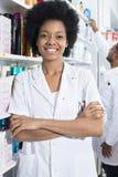 Βέβαιος θηλυκός φαρμακοποιός με τα όπλα που διασχίζονται στο φαρμακείο στοκ εικόνες με δικαίωμα ελεύθερης χρήσης