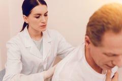 Βέβαιος ιατρικός εργαζόμενος που κάνει το μασάζ Στοκ Εικόνα