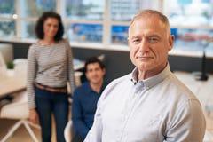 Βέβαιος διευθυντής που στέκεται σε ένα γραφείο με το προσωπικό πίσω από τον Στοκ Φωτογραφία