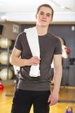 Βέβαιος και χαμογελώντας νεαρός άνδρας που ασκεί στη γυμναστική ικανότητας Στοκ Εικόνες