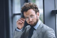 Βέβαιος μοντέρνος επιχειρηματίας eyeglasses και κοστούμι που εξετάζει τη κάμερα Στοκ Εικόνες