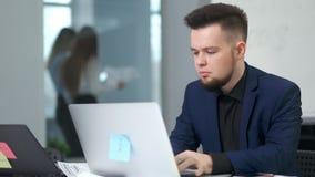 Βέβαιος μοντέρνος νέος επιχειρηματίας πορτρέτου που φορά το κοστούμι που χρησιμοποιεί τη συνεδρίαση PC στον πίνακα στο σύγχρονο γ απόθεμα βίντεο