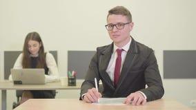 Βέβαιος νέος αρσενικός διευθυντής στη συνεδρίαση κοστουμιών στο γραφείο στο πρώτο πλάνο που κοιτάζει στη κάμερα Ελκυστικές νεολαί απόθεμα βίντεο