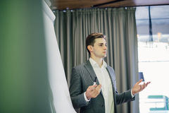 Βέβαιος νέος αρχηγός ομάδας ή διευθυντής που στέκεται μπροστά από ένα διάγραμμα κτυπήματος και ένα παρόν πρόγραμμα για το γραφείο Στοκ Εικόνα