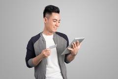 Βέβαιος νέος ασιατικός επιχειρηματίας που κρατά την ψηφιακή ταμπλέτα ανατρέχοντας Στοκ φωτογραφία με δικαίωμα ελεύθερης χρήσης