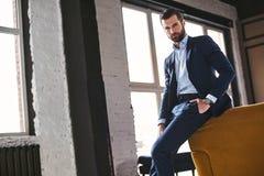 Βέβαιος νέος γενειοφόρος brunet στο κομψό κοστούμι εξετάζει τη κάμερα στοκ φωτογραφίες με δικαίωμα ελεύθερης χρήσης