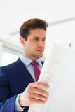 Βέβαιος νέος επιχειρηματίας που αναλύει το σχεδιάγραμμα στο νέο γραφείο Στοκ Φωτογραφίες