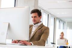 Βέβαιος νέος επιχειρηματίας που εργάζεται στον υπολογιστή με τη γυναίκα συνάδελφος στο υπόβαθρο στο γραφείο Στοκ Εικόνες