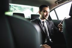 Βέβαιος νέος επιχειρηματίας που θέτει το έξυπνο τηλέφωνό του και που εξετάζει τη κάμερα καθμένος στο αυτοκίνητο Στοκ φωτογραφία με δικαίωμα ελεύθερης χρήσης