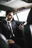 Βέβαιος νέος επιχειρηματίας που θέτει το έξυπνο τηλέφωνό του και που εξετάζει τη κάμερα καθμένος στο αυτοκίνητο Στοκ Εικόνες