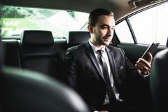 Βέβαιος νέος επιχειρηματίας που θέτει το έξυπνο τηλέφωνό του και που εξετάζει τη κάμερα καθμένος στο αυτοκίνητο Στοκ Εικόνα
