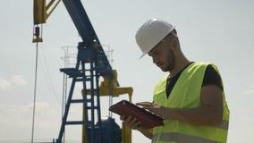 Βέβαιος νέος μηχανικός που αναλύει το πρόγραμμα για την επεξεργασία δραστηριότητας πετρελαίου στην ταμπλέτα του - απόθεμα βίντεο