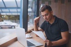 Βέβαιος νεαρός άνδρας που εργάζεται στο lap-top στο παράθυρο Στοκ Εικόνες