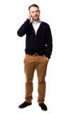 Βέβαιος νεαρός άνδρας που κουβεντιάζει σε κινητό του Στοκ Φωτογραφίες