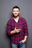 Βέβαιος νεαρός άνδρας που κρατά το έξυπνο τηλέφωνο και που εξετάζει τη κάμερα στεμένος στο γκρίζο κλίμα Στοκ εικόνες με δικαίωμα ελεύθερης χρήσης
