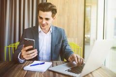 Βέβαιος νεαρός άνδρας στην έξυπνη περιστασιακή ένδυση που κρατά το έξυπνο τηλέφωνο και που εξετάζει το καθμένος στη θέση εργασίας Στοκ φωτογραφία με δικαίωμα ελεύθερης χρήσης