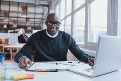 Βέβαιος νεαρός άνδρας στο γραφείο του Στοκ φωτογραφία με δικαίωμα ελεύθερης χρήσης