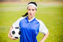 Βέβαιος ποδοσφαιριστής που στέκεται με μια σφαίρα Στοκ Εικόνα