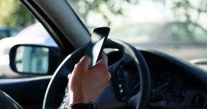 Βέβαιος στο δρόμο Συνεδρίαση νεαρών άνδρων στο πρόσφατα αγορασμένο αυτοκίνητό του με την οδήγηση ασφαλιστικής ασφάλειας smartphon φιλμ μικρού μήκους