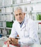 Βέβαιος φαρμακοποιός που κλίνει στο μετρητή στο φαρμακείο στοκ εικόνες