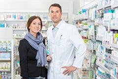 Βέβαιος φαρμακοποιός που στέκεται με τον πελάτη μέσα στοκ εικόνες