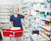 Βέβαιος φαρμακοποιός που τακτοποιεί τα φάρμακα στα ράφια στοκ εικόνα με δικαίωμα ελεύθερης χρήσης