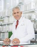 Βέβαιος φαρμακοποιός που χαμογελά στο μετρητή στο φαρμακείο στοκ φωτογραφία