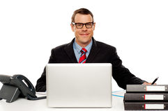 Βέβαιος χαμογελώντας αρσενικός ανώτερος υπάλληλος που φορά τα γυαλιά Στοκ Εικόνα