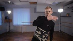 Βέβαιος χορευτής χιπ χοπ που χορεύει και που εξετάζει ενεργά τη κάμερα σε ένα στούντιο χορού Ο νεαρός άνδρας εκτελεί τις κινήσεις φιλμ μικρού μήκους