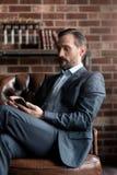 Βέβαιος όμορφος επιχειρηματίας που εξετάζει το κινητό τηλέφωνό του Στοκ εικόνα με δικαίωμα ελεύθερης χρήσης