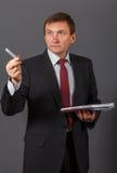 Βέβαιος ώριμος επιχειρηματίας που στέκεται μπροστά από ένα γκρίζο backgro Στοκ Εικόνες