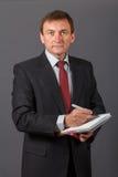 Βέβαιος ώριμος επιχειρηματίας που στέκεται μπροστά από ένα γκρίζο backgro Στοκ Εικόνα