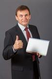 Βέβαιος ώριμος επιχειρηματίας που στέκεται μπροστά από ένα γκρίζο backgro Στοκ φωτογραφία με δικαίωμα ελεύθερης χρήσης