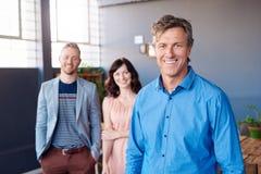 Βέβαιος ώριμος businesoman με τους χαμογελώντας συναδέλφους που στέκονται στο υπόβαθρο Στοκ φωτογραφίες με δικαίωμα ελεύθερης χρήσης