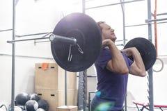 Βέβαιο άτομο που ανυψώνει barbell στη γυμναστική crossfit στοκ φωτογραφίες