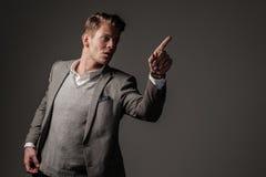 Βέβαιο αιχμηρό ντυμένο άτομο στο γκρίζο σακάκι Στοκ Φωτογραφία
