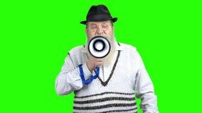 Βέβαιο ανώτερο άτομο που μιλά με megaphone απόθεμα βίντεο