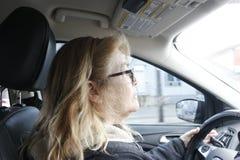 Βέβαιο ανώτερο οδηγώντας αυτοκίνητο γυναικών στοκ εικόνα