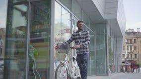 Βέβαιο ελκυστικό άτομο αφροαμερικάνων πορτρέτου που στέκεται με το ποδήλατο στα πλαίσια της αστικής αρχιτεκτονικής φιλμ μικρού μήκους