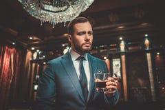 Βέβαιο καλά-ντυμένο άτομο με το ποτήρι του ουίσκυ στο εσωτερικό διαμερισμάτων πολυτέλειας Στοκ Φωτογραφίες