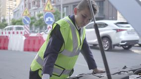 Βέβαιο μικρό παιδί που φορά τον εξοπλισμό ασφάλειας που υπερασπίζεται την ανοικτή κουκούλα ενός σπασμένου αυτοκινήτου Αγόρι που ε απόθεμα βίντεο