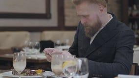 Βέβαιο ξανθό γενειοφόρο άτομο πορτρέτου στο μοντέρνο σακάκι που παίρνει μια φωτογραφία των τροφίμων του με τη συνεδρίαση κινητών  απόθεμα βίντεο