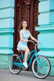 Βέβαιο όμορφο θηλυκό που οδηγά το μπλε ποδήλατο που περνά το παλαιό μπλε κτήριο με τις κόκκινες πόρτες στη θερινή ημέρα Στοκ εικόνα με δικαίωμα ελεύθερης χρήσης