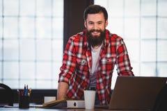 Βέβαιο hipster που κλίνει στο γραφείο στο δημιουργικό γραφείο Στοκ εικόνα με δικαίωμα ελεύθερης χρήσης