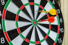 Βέλη βελών που χτυπούν στο κέντρο στόχων του dartboard Στοκ εικόνα με δικαίωμα ελεύθερης χρήσης